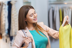 Happy young woman choosing clothes in mall Stock Photography