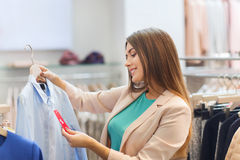Happy young woman choosing clothes in mall Royalty Free Stock Photo