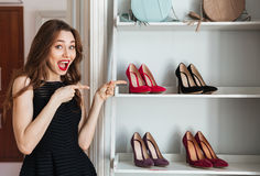 Happy young woman choosing shoes and pointing. Royalty Free Stock Photos
