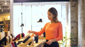 Happy young woman choosing shoes at store stock footage