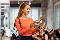 Happy young woman choosing shoes at store Stock Photo
