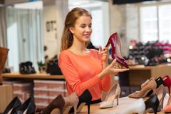 Happy young woman choosing shoes at store Royalty Free Stock Image