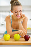 Happy young woman choosing between two green and one red apple Royalty Free Stock Image
