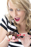 Happy Young Woman Choosing Which Chocolates to eat Stock Image
