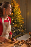 Happy young woman chopping walnuts  in kitchen Royalty Free Stock Image