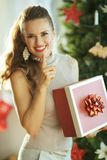 Happy young woman with Christmas gift showing shh gesture stock photo