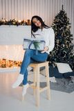 Happy Young Woman With Christmas Gift surprised and excited sitting at home against xmas decorations Royalty Free Stock Photo