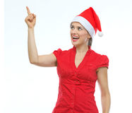 Happy young woman in Christmas hat pointing up Stock Photos
