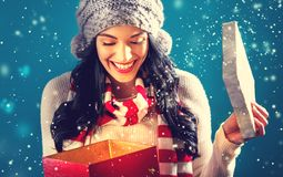 Happy young woman with Christmas present box. Happy young woman opening a Christmas present box Royalty Free Stock Image