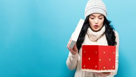 Happy young woman with Christmas present box. Happy young woman opening a Christmas present box Royalty Free Stock Photos