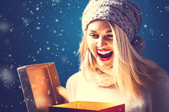 Happy young woman with Christmas present box. Happy young woman opening a Christmas present box Royalty Free Stock Photography