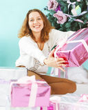 Happy young woman with Christmas present in her hands Royalty Free Stock Photos