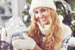 Happy young woman with Christmas present in her hands Royalty Free Stock Photography