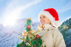 Happy young woman with Christmas tree in the front of mountains Royalty Free Stock Photography