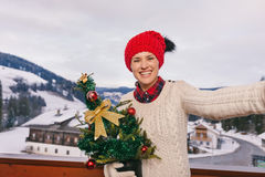 Happy young woman with Christmas tree taking selfie on balcony Royalty Free Stock Image