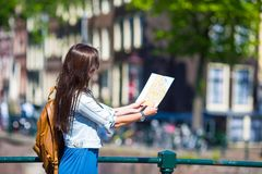 Happy young woman with a city map and backpack in Royalty Free Stock Image