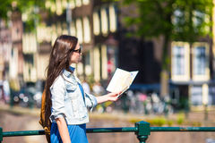 Happy young woman with a city map and backpack in Royalty Free Stock Photos