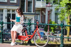 Happy young woman with a city map on bike in european city. Happy young woman with a city map smiling riding on bicycle Royalty Free Stock Photos