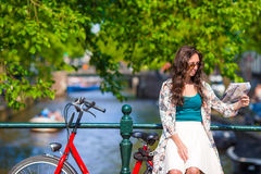 Happy young woman with a city map on bike in Royalty Free Stock Photo
