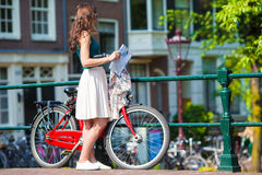 Happy young woman with a city map on bike in Stock Images