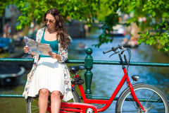 Happy young woman with a city map on bike in Stock Photo