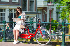 Happy young woman with city map and bikes in Stock Photography
