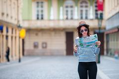 Happy young woman with a city map in city. Travel tourist woman with map in Prague outdoors during holidays in Europe. Travel tourist woman with map in Prague royalty free stock photography