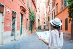 Happy young woman with a city map on desert street in Europe. Travel tourist woman with map in Rome outdoors during Royalty Free Stock Images