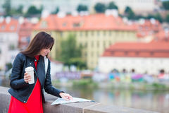 Happy young woman with a city map in Europe. Travel tourist woman with map outdoors during holidays in Europe. stock images