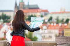 Happy young woman with a city map in Europe. Travel tourist woman with map outdoors during holidays in Europe. Travel tourist woman with map in Prague outdoors royalty free stock photography