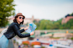 Happy young woman with a city map in Europe. Travel tourist woman with map in Prague outdoors during holidays in Europe. Travel tourist woman with map in Prague stock photo