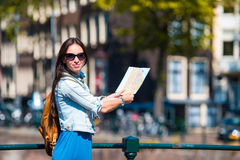 Happy young woman with a city map in european city Stock Images