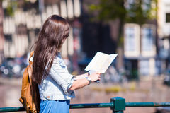 Happy young woman with a city map in european city Stock Photo