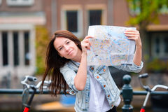 Happy young woman with a city map in european city Royalty Free Stock Images