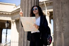 Happy young woman with a city map in hands, showing a finger up, have a backpack smiling, over cathedral background. royalty free stock images