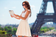Happy young woman with a city map in Paris background the Eiffel tower Stock Images
