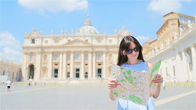 Happy young woman with city map in Vatican city and St. Peter`s Basilica church, Rome, Italy. Travel tourist woman with. Happy young woman with a city map in stock footage