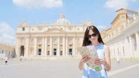 Happy young woman with city map in Vatican city and St. Peter`s Basilica church, Rome, Italy. Travel tourist woman with