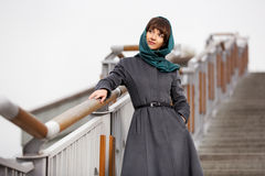 Happy young woman in classic coat on the steps Royalty Free Stock Photography