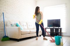 Attractive smiling woman cleaning the floor with a mop. Happy young woman cleaning floor with mop in living room Royalty Free Stock Photos