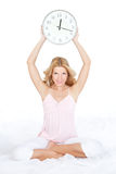 Happy young woman with clock on the bed Royalty Free Stock Photos