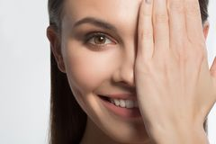 Happy young woman closing eye by hand stock photography
