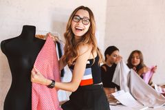 Happy young woman clothes designer at the atelier stock photo