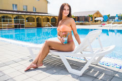 Happy young woman with cocktail laying on chaise lounge. Time summer photo. Happy young woman with cocktail laying on chaise lounge stock image