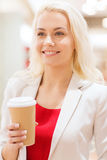 Happy young woman with coffee paper cup in mall Stock Photography