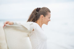 Happy young woman on cold beach rejoicing Royalty Free Stock Image