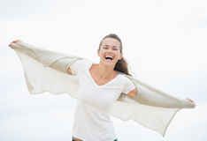 Happy young woman on cold beach rejoicing Stock Photo