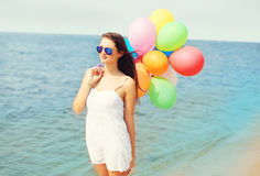 Happy young woman with colorful balloons on beach near sea Stock Photography
