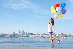 Happy young woman with colorful balloons Stock Photo