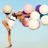 Happy young woman with colorful latex balloons Stock Images